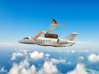 Young woman sitting on airplane above clouds