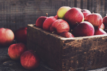 Rustic wooden crate with ripe apples with empty space on wooden background