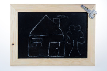 Funny sketch of house with tree and key on blackboard