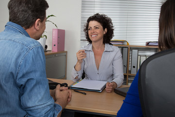 Couple at meeting with an adviser female at desk
