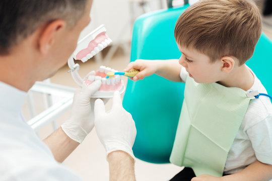 Dentist teaching little boy bruching teeth in dental clinic