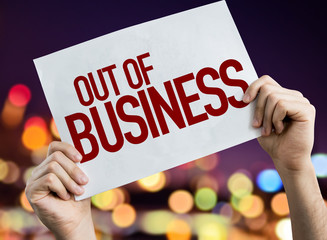 Out Of Business placard with night lights on background