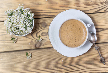 Vintage cup of coffee and flowers on wooden table