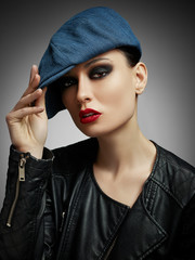 Portrait of girl with bright makeup in black leather jacket and jeans cap on a dark background