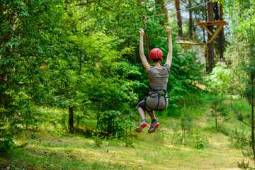Young woman climbing in adventure climbing high wire park