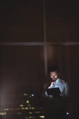 Businessman using tablet at night