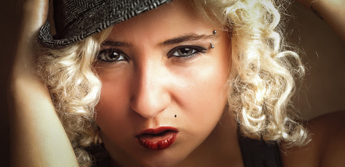 Beautiful woman in hat with red lips, business style. Blonde girl holding her hands near to the face, attractive woman with beautiful eyes. Handsome woman with sensual lips in gangster style.