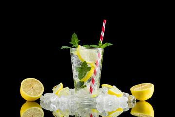 Lemon water in glass on black background