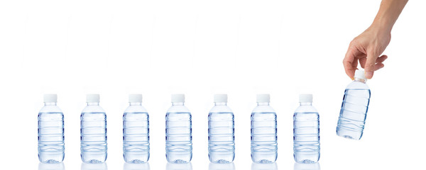 Male's hand grabs and holds a bottle of water with another bottl