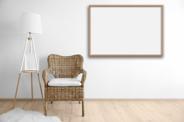 Cozy chair with lamp and empty picture frame on wall background