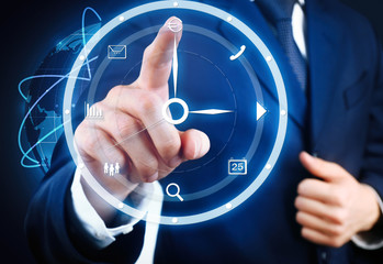 Businessman hand pushing time icon on virtual screen.