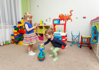 Two children play with plastic rings in kindergarten