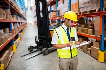 Warehouse manager checking list on his clipboard