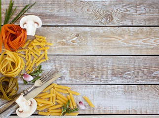 Spaghetti of different flowers and forms with vegetables and spices on a wooden background