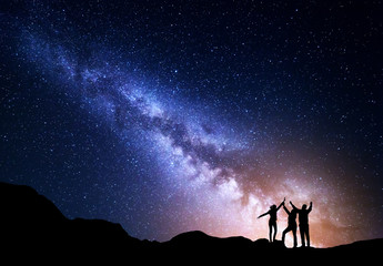 Landscape with colorful Milky Way and yellow light. Night starry sky with silhouette of a sporty happy family with raised-up arms on the rock. Beautiful Universe. Space background