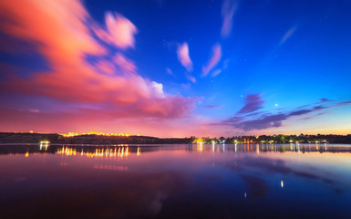 Colorful night landscape on the lake with blue sky and moving clouds reflected in water. Nature background