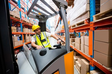 Warehouse manager driving a forklift