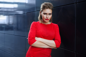 beautiful girl with make-up in a red dress in a modern city, space for text