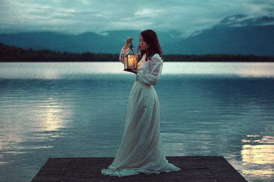 Sad bride on lake pier with lantern