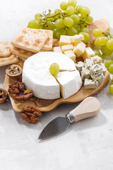 camembert, grapes and crackers on a white background, vertical