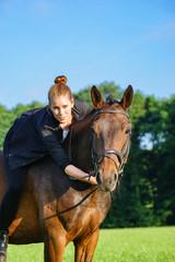 Attraktive, junge Frau mit Pferd auf einer Wiese