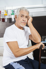 Sad Male Patient Holding Cane At Rehab Center