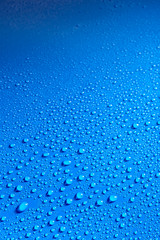 Shiny blue smooth surface covered with dew drops