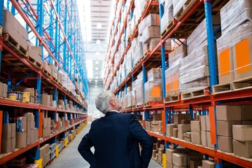 Warehouse manager turns back to the camera and looking up