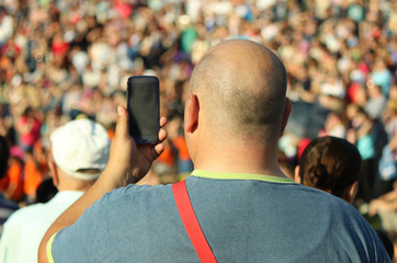 Man shooting photos in a crowd on his mobile phone