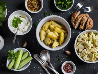 Baked cauliflower and potatoes, fresh cucumbers and herbs, sauces and spices on a dark stone background. Healthy vegetarian lunch or snack in a rustic style. Top view