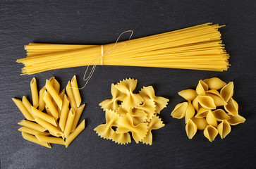 Various types of pasta on black background, from above