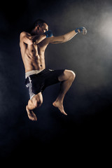 Wall Murals Martial arts Muscular kickbox or muay thai fighter punching in jump. Smoke.