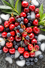 Berries background and Ice cubes in the shape of heart . Summer