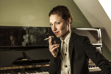 Young woman in men's black suit smoking cigarette sensual near a