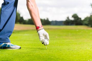 Man putting golf ball on tee, close shot