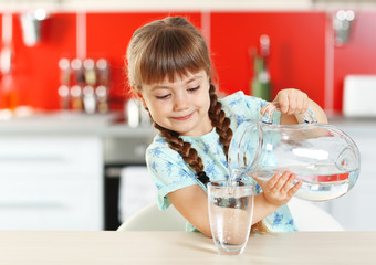 Adorable little girl pouring water in kitchen