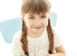 Cute little girl holding glass of water on light background