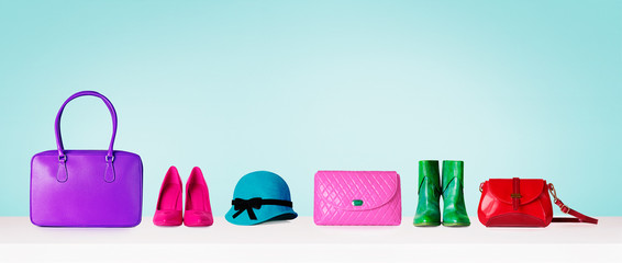 Woman accessories shopping items isolated on pastel color blue background. Shoes and purse bags and hat. with copy space.