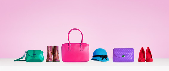 Colorful hand bags,purse,shoes, and hat isolated on pink background. Woman fashion accessories items. Shopping image.