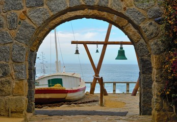 View through and arch onto the ocean outside of Pablo Nerudas house with a wooden construction with green bells and a white boat in the foreground