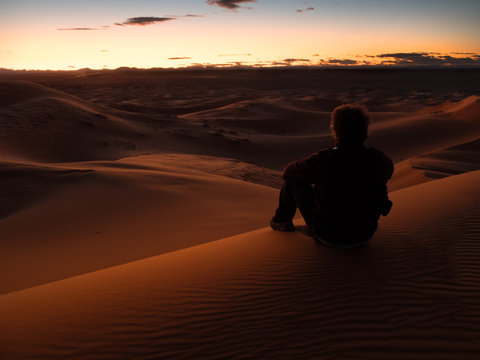 man sitting on a dune in the desert while watching the sunset. Morocco.