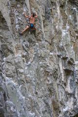 Rock Climber climbing a steep cliff on a mountain. Taken near Squamish, British Columbia, Canada