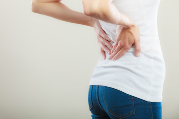 Backache. Young woman suffering from back pain