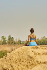 Skinny girl doing yoga on cliff