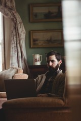 Portrait of hipster man using laptop while resting in the sofa