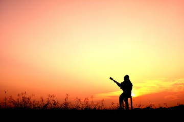 Silhouette women playing guitar in the sunset