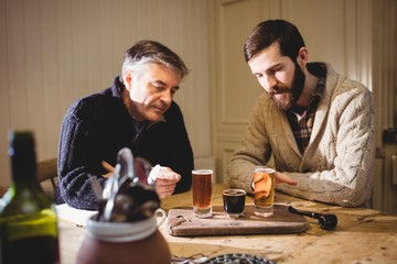 Mature and hipster man looking at shot on the table