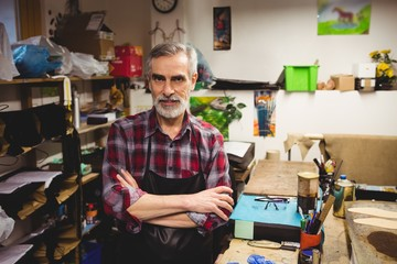 Portrait of cobbler standing in workshop