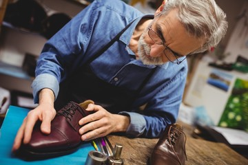Tilted view of cobbler examining a shoe