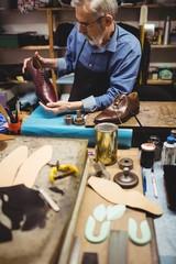 Cobbler examining a shoe